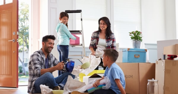 Family unpacking boxes in newly moved home
