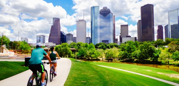 Couple cycling to downtown Houston along parkway