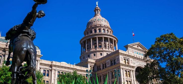 Texas state capitol building with statue of cowboy riding a horse
